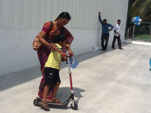 Parent Encouraging Her Child To Try The Scooter
